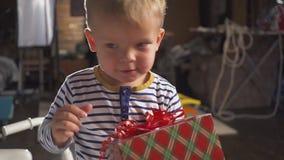 Dwa roczniaka słodka chłopiec dostaje prezent z czerwonym faborkiem za choinką z innymi udziałami prezentów pudełka zbiory wideo