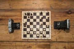 Dwa rocznik kamery bawić się szachy na drewnianej desce ustawiają na niektóre Obraz Royalty Free