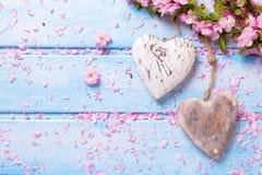 Dwa rocznika dekoracyjnego serca i różowego Sakura kwitną na błękitnym w Fotografia Stock