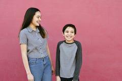 Dwa rodzeństw dzieci stojak Przeciw Różowi Ścienny Śmiać się zabawę i Mieć zdjęcie royalty free