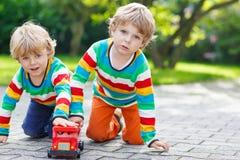 Dwa rodzeństwa, dzieciak chłopiec bawić się z czerwonym autobusem szkolnym Fotografia Stock