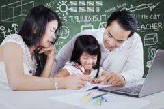 Dwa rodzica i ich dziecko robi pracie domowej zdjęcie royalty free