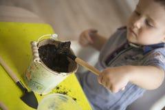 Dwa roku chłopiec ogrodnictwa puszkuje rośliny Zdjęcia Royalty Free