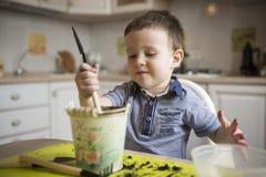 Dwa roku chłopiec ogrodnictwa puszkuje rośliny Obraz Royalty Free
