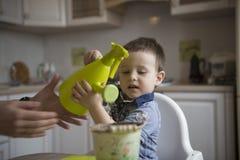 Dwa roku chłopiec ogrodnictwa puszkuje rośliny Obrazy Royalty Free