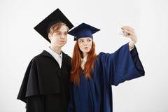 Dwa rozochoconego absolwenta błaź się robi selfie nad białym tłem uniwersytet Obraz Stock