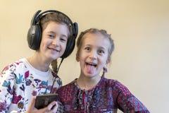 Dwa rozochoconego dziewczyn 5 i 7 lat słucha muzyka na smartphone Obrazy Stock