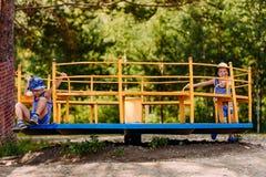 Dwa rozochoconej chłopiec w kapeluszach i koszulkach bawić się na dużym żelaznym carousel na boisku obrazy royalty free