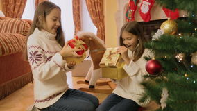 Dwa rozochoconej dziewczyny daje Bożenarodzeniowym teraźniejszość each inny i otwiera one zdjęcie wideo