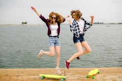 Dwa rozochoconej szczęśliwej łyżwiarki dziewczyny w modnisia stroju ma zabawę na drewnianym molu podczas wakacje fotografia royalty free