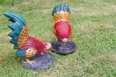 Dwa rzeźb koguta stojak na ogródzie Fotografia Stock