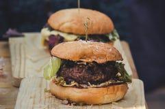 Dwa rzemiosło wołowiny hamburgeru na drewnianym stole odizolowywającym obrazy royalty free