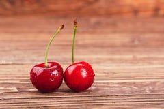 Dwa słodkiej wiśni jagody na drewnianym tle Fotografia Royalty Free