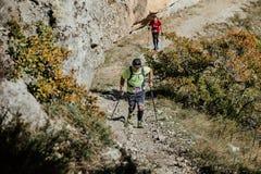 Dwa samiec atleta z chodzącymi słupami chodzić ciężkiego na tło zwykłej falezie Fotografia Stock