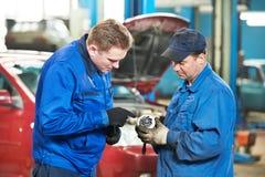 Dwa samochodowy mechanik diagnozuje auto parowozowego problem fotografia royalty free
