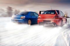Dwa samochodu współzawodniczą w rasie przy zima zmierzchem Zdjęcie Stock