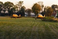 Dwa samolotów żółty stojak pred zdejmuje przy zielonym trawiastym lotniskiem zdjęcie royalty free