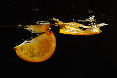 Dwa segmentu dojrzała pomarańcze spadać w wodę Obrazy Stock