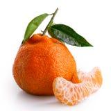 Dwa segmentu mandarynka obok całej mandarynki z liśćmi są Fotografia Stock