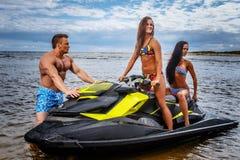 Dwa seksownej dziewczyny w swimsuit i bez koszuli mięśniowej samiec, zabawę z dżetową nartą na morzu obrazy stock