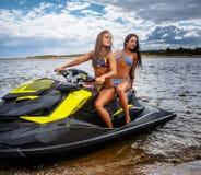 Dwa seksownej dziewczyny w swimwear, siedzi na dżetowej narcie, zabawę przy czasem wolnym zdjęcie royalty free