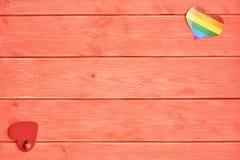 Dwa serca kłamają na drewnianym tło kolorze żywy koral Jeden serce z tęczą LGBT społeczność i inna czerwień obrazy stock