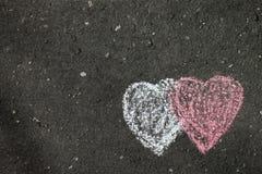 Dwa serca malującego na popielatym asfalcie obraz stock