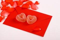Dwa serca od cukrowych cukierków na czerwonej kopercie i płatkach zdjęcie royalty free