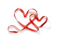 Dwa serca od czerwonego faborku na białym tle obrazy royalty free