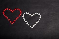 Dwa sercowatego czerwonego i białych cukierku na czarnym tle fotografia royalty free