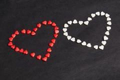 Dwa sercowatego czerwonego i białych cukierku na czerni zdjęcia stock