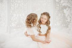 Dwa siostr Pięknego dziecka dziewczyna w biel sukni na tła mienia kryształach fotografia stock