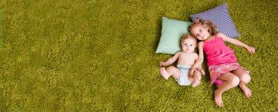 Dwa siostr szczęśliwy kłamstwo na dywanie Zdjęcia Royalty Free