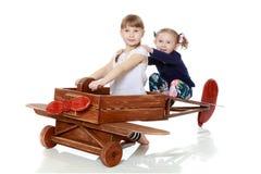 Dwa siostry bawić się w drewnianym samolocie Obrazy Stock
