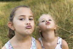 Dwa siostry bawić się - z jeden ręką zakrywa usta inny, aga Obrazy Stock