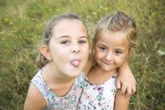 Dwa siostry bawić się - z jeden ręką zakrywa usta inny, aga Zdjęcie Royalty Free