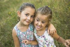 Dwa siostry bawić się - z jeden ręką zakrywa usta inny, aga Zdjęcie Stock