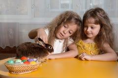 dwa siostry bawić się z Wielkanocnym królikiem Zdjęcia Royalty Free