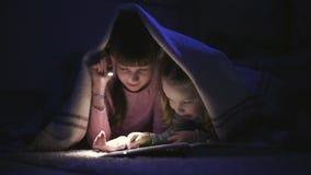 Dwa siostry czyta książkę pod koc z latarką w ciemnym pokoju przy nocą zbiory wideo