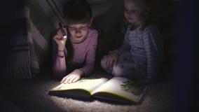 Dwa siostry czyta ksi??k? pod koc z latark? w ciemnym pokoju przy noc? zbiory wideo
