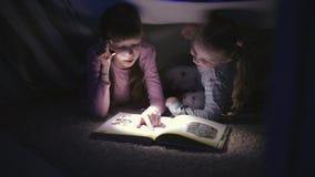 Dwa siostry czyta ksi??k? pod koc z latark? w ciemnym pokoju przy noc? zbiory