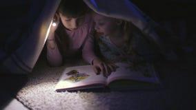 Dwa siostry czyta ksi??k? pod koc z latark? w ciemnym pokoju przy noc? zdjęcie wideo