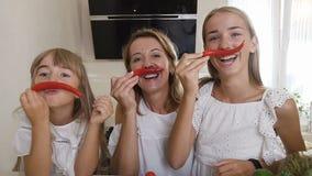 Dwa siostry i ich matka ubierający w biel ubraniach mają zabawę z chili pieprzem w kuchni w domu giro zbiory
