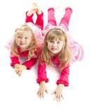 Dwa siostry kłaść w dół ono uśmiecha się zdjęcia stock
