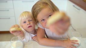 Dwa siostry, małe dziewczynki siedzi wpólnie przy stołowym cieszy się łasowanie domem zrobili ciastkom, dunking one w szkła zbiory