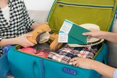 Dwa siostry pakuje walizkę na żywej izbowej kanapie Fotografia Stock