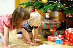 Dwa siostry patrzeje dla prezentów pod drzewem Fotografia Royalty Free