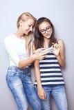 Dwa siostry pozuje z telefonem komórkowym Zdjęcia Royalty Free