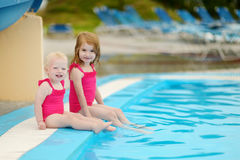 Dwa siostry siedzi pływackim basenem Obraz Royalty Free