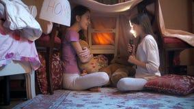 Dwa siostry siedzi pod koc przy sypialnią i mówi opowieści z latarką zbiory wideo